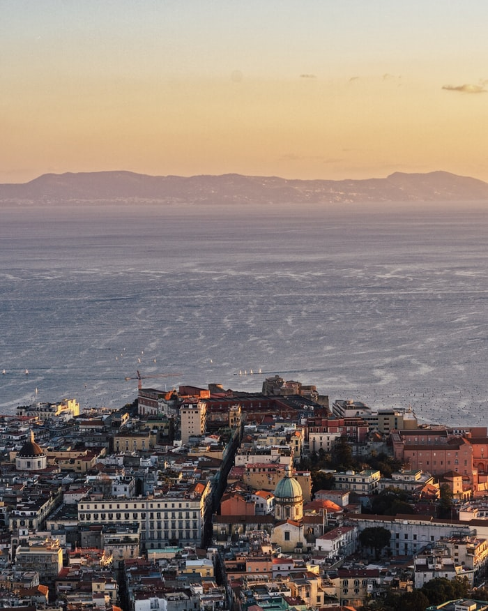 a view over the city of naples in italy, where to go in europe, european cities to visit and enjoy the beach and city