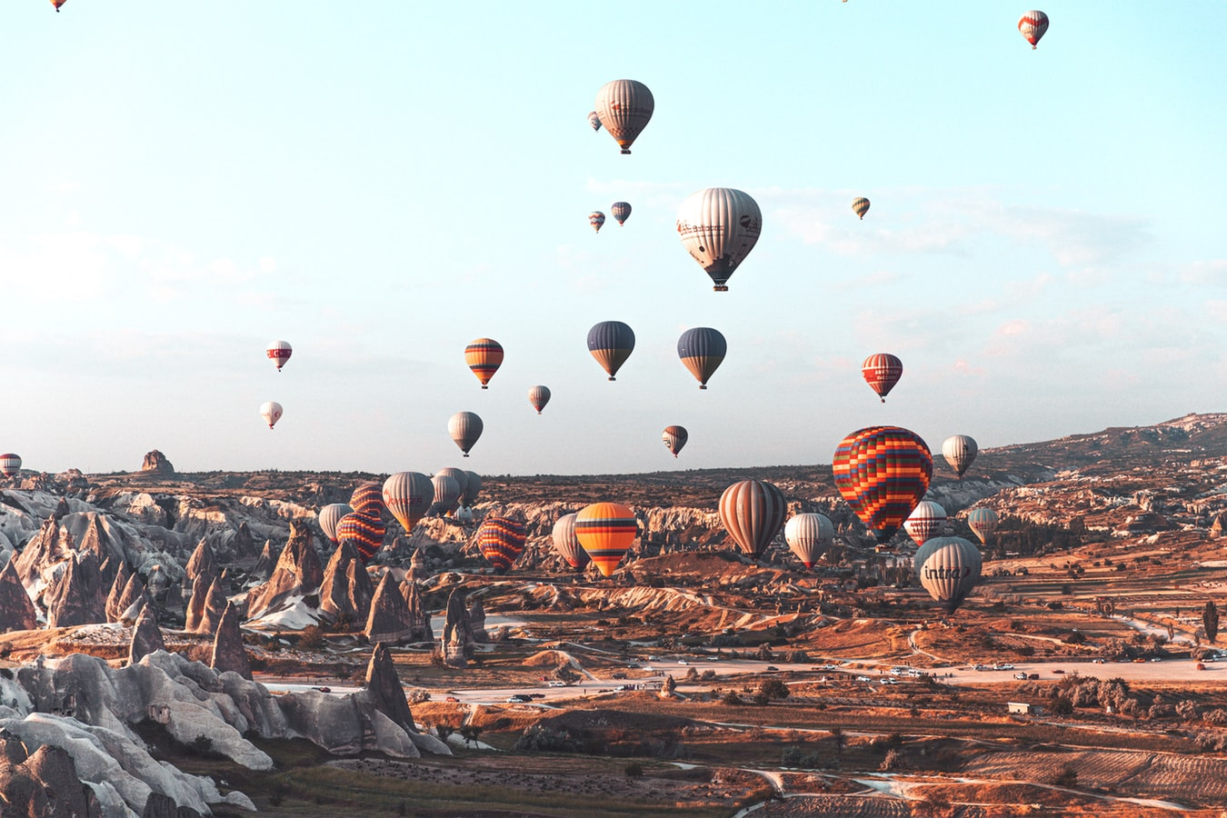 hot air balloons in cappadocia in turkey, view over landscape and blue sky with mountains