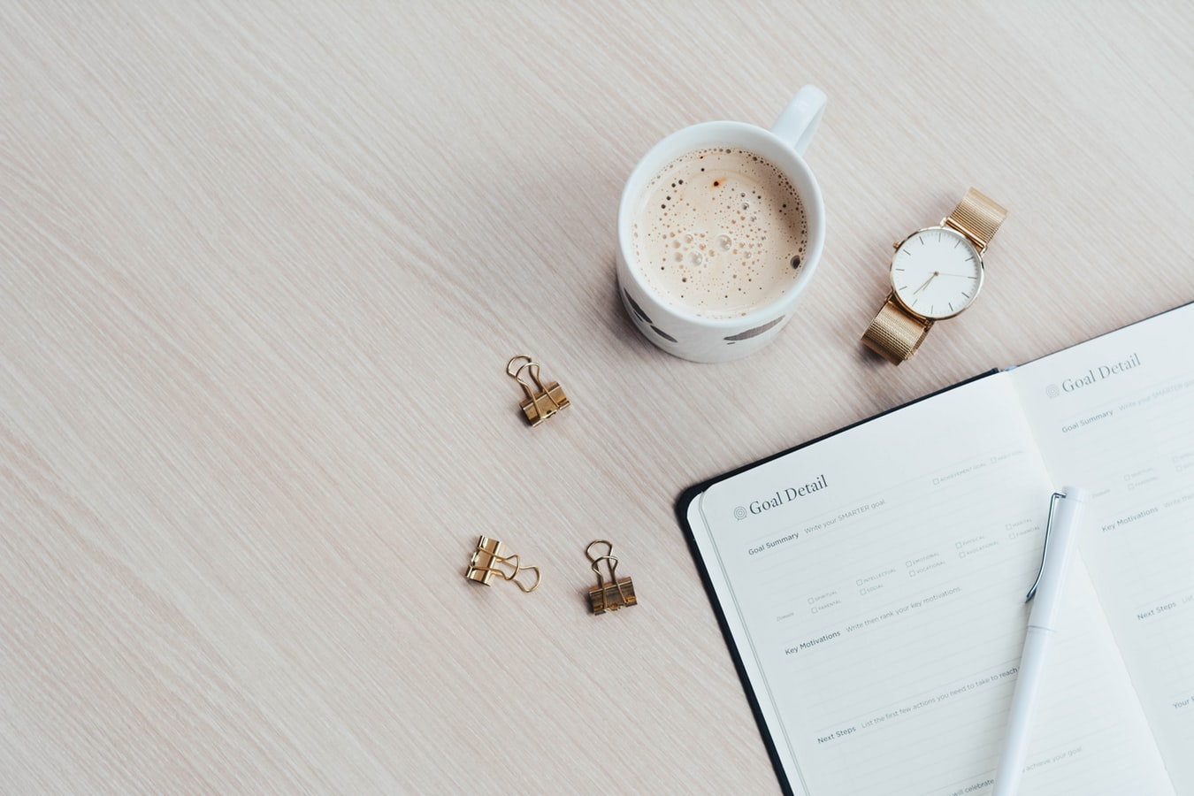 coffee on a table with a planner next to it, how to increase productivity at home