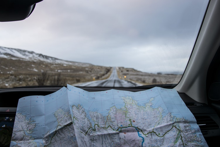 Road trip with snowy mountains and a world map