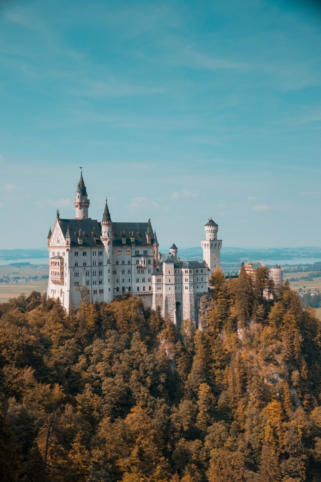 a castle in germany on a mountain with a blue sky, 20 trips to take in your 20s