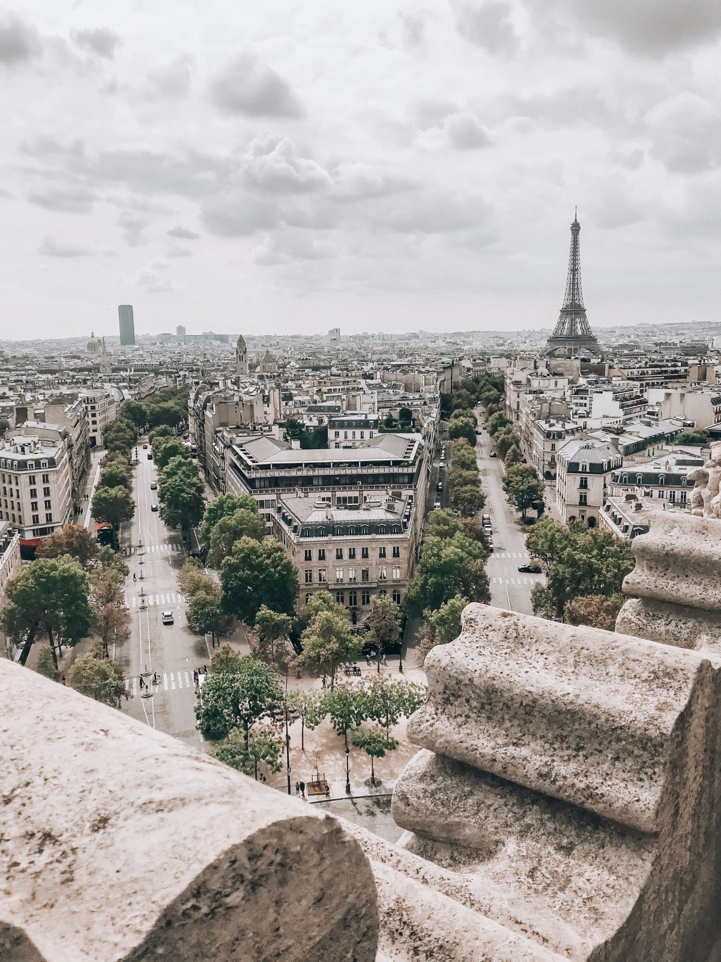 the view over Paris from the Arc de Triomph on a cloomy day, the Eiffel Tower in the distance, travel