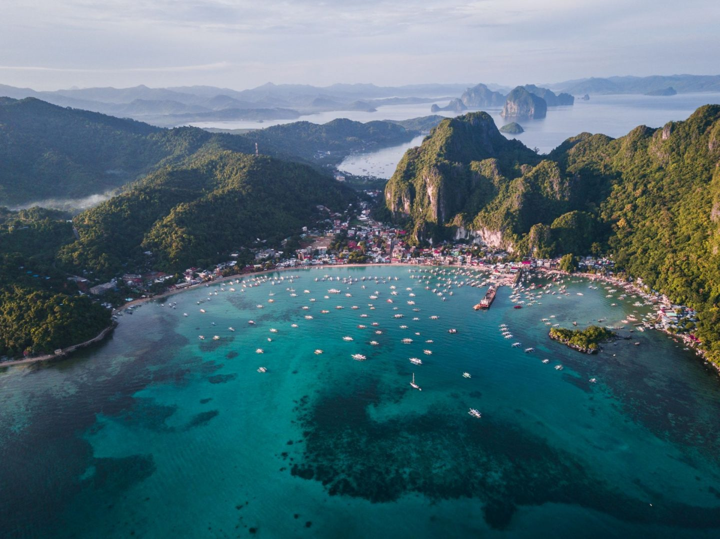 picture of the philippines with boats in the ocean near a village, islands of the philippines, palawan, islands located in asia, blue water and green mountains