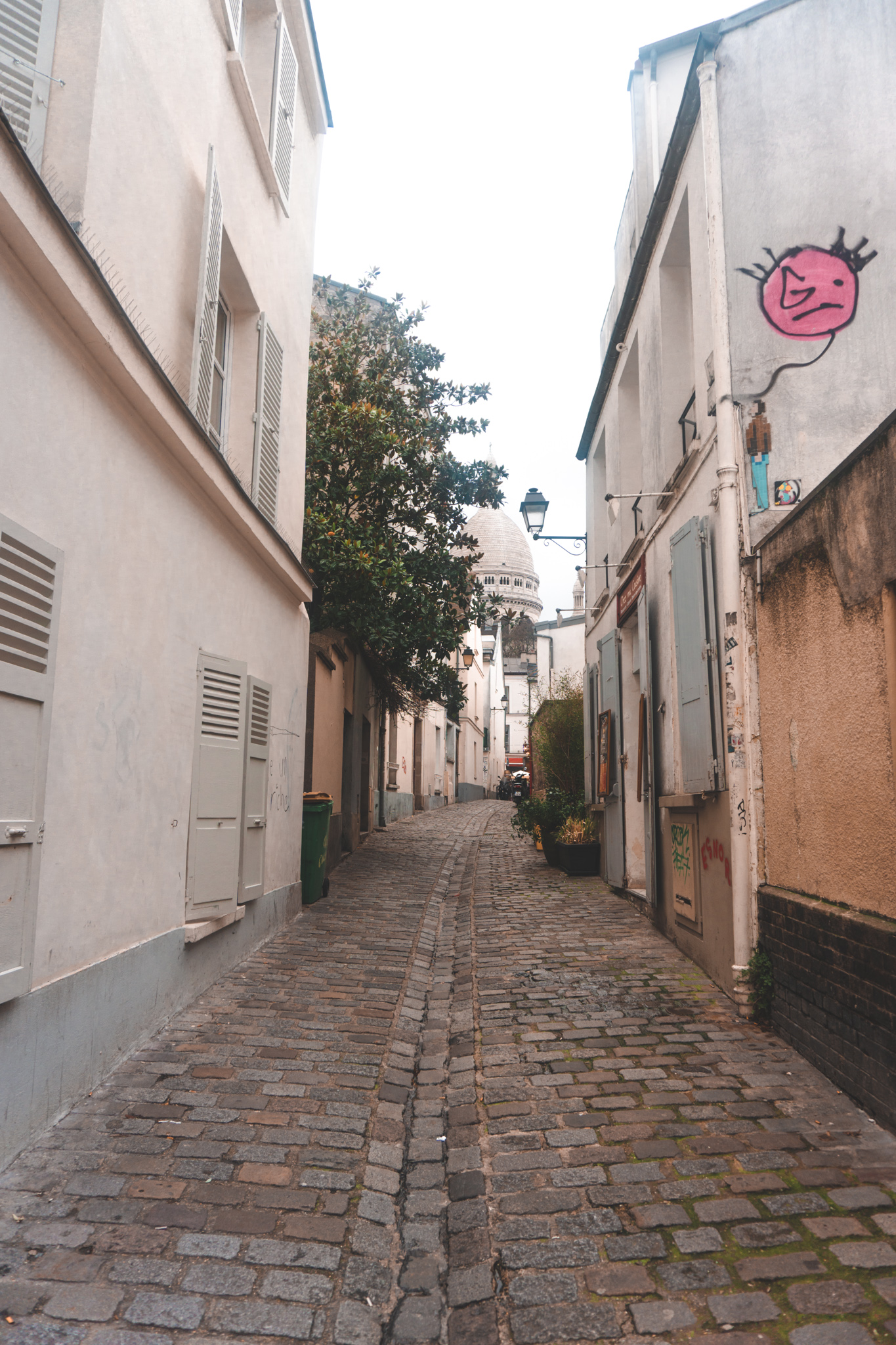 back street in montmartre with the sacre coeur in the background, paris guide, montmartre guide