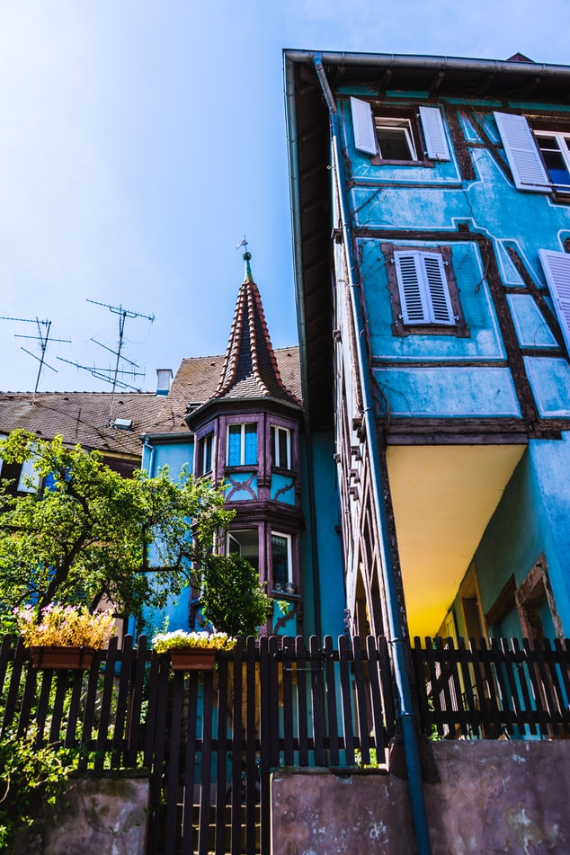 postcard fairy tales villages, house with blue and yellow accents in colmar, france
