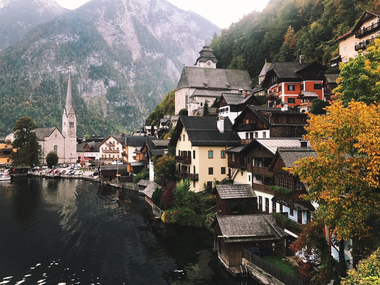 hallstatt in austria, village next to the lakes in between the mountains with trees