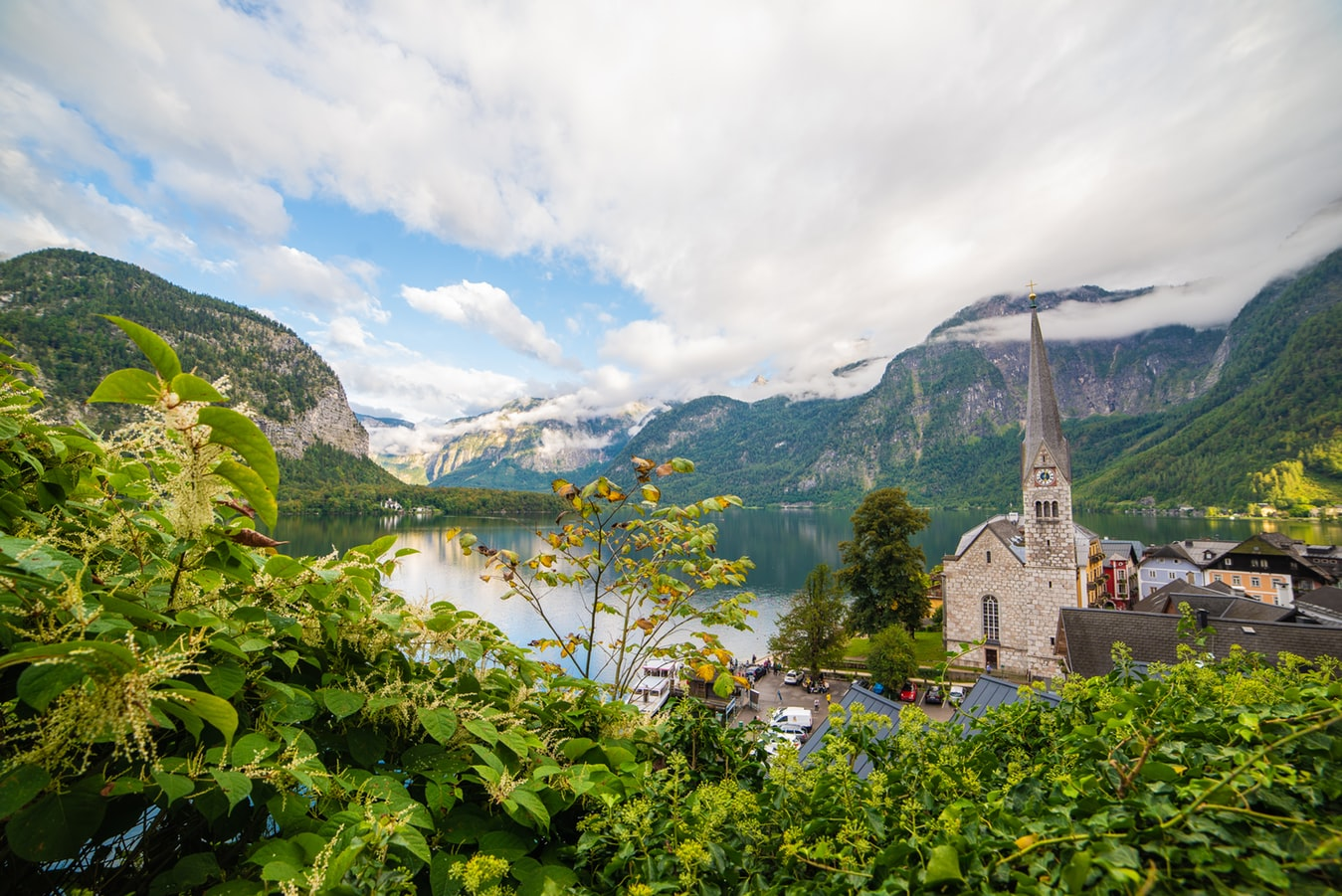 hallstatt village in austria, church next to the lake in between mountains, fairy tale villages