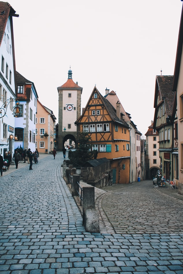 a street in the city rothenburg in germany with houses and church, fairy tale villages