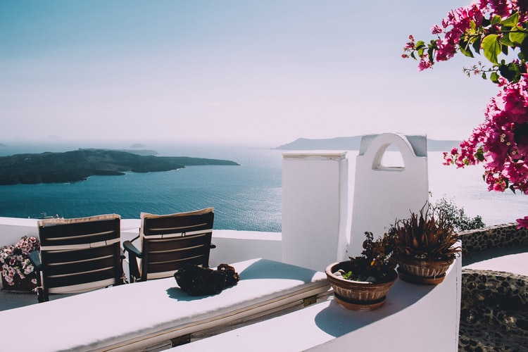 view over the ocean from a terrace in santorini, flowers on greece islands