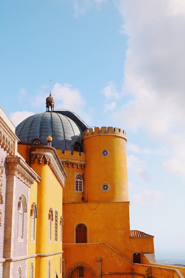 yellow castle in sintra in portugal, fairy tale villages to visit worldwide, travel inspiration