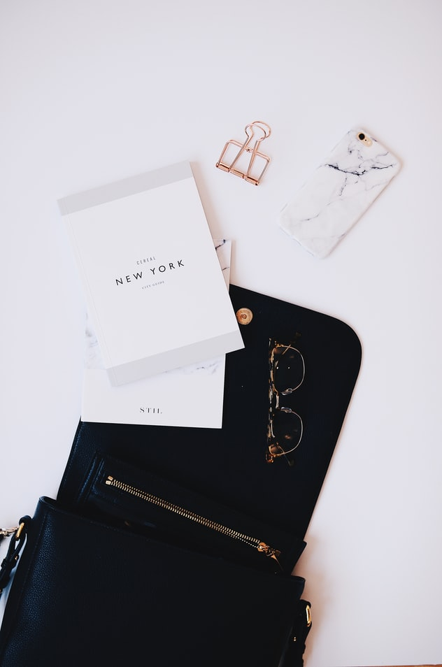 a bag, planner, a phone and sunglasses on a white background