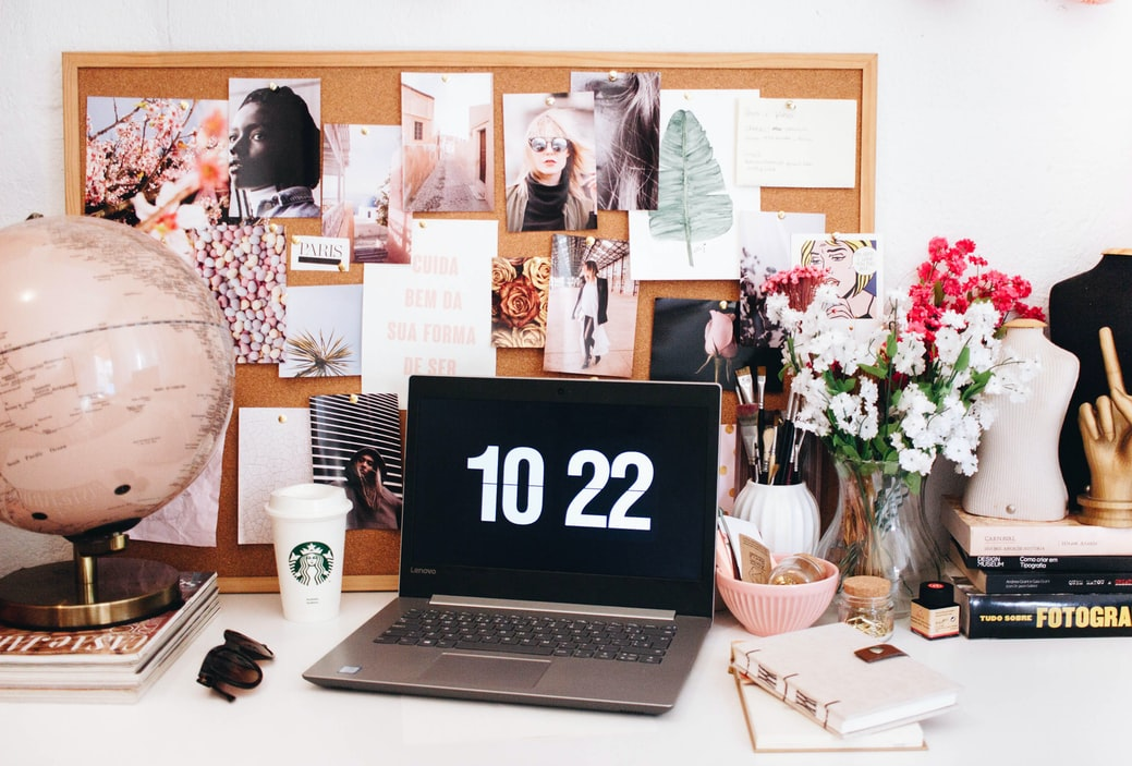 laptop on a desk with flowers and paintings, the truth behind having a travel blog