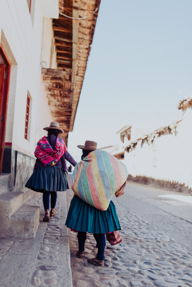 two people from the local community walking on a street, slow travelling as a way to travel, bags and houses
