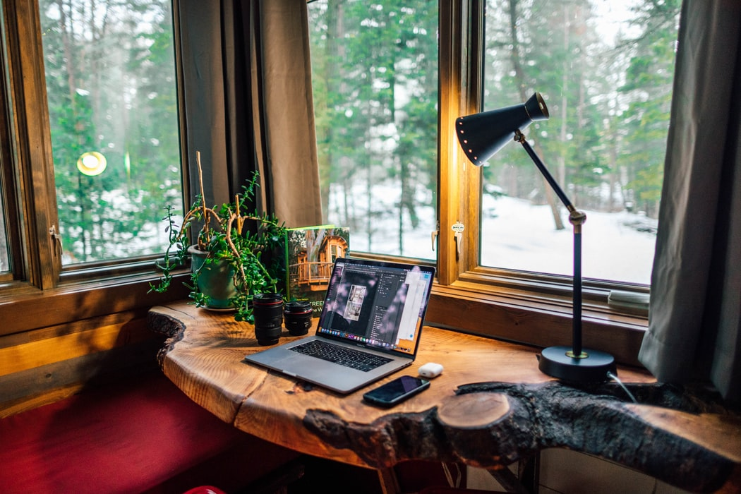 a desk lamp next to a desk with a laptop on it, desk essentials for your home office