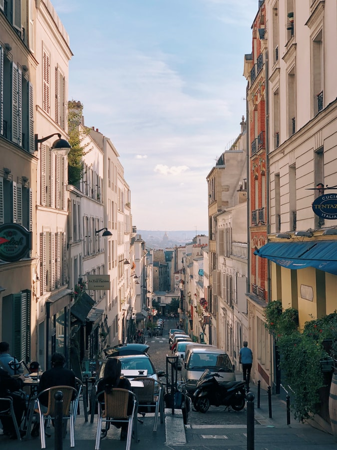 pretty street in paris with a blue sky and cars, paris quotes and travel quotes