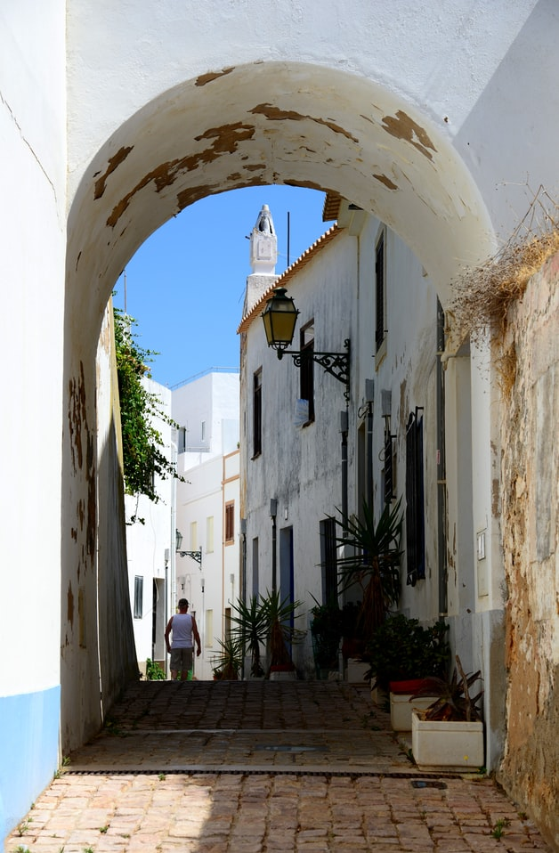 a street in albufeira in portugal, blue sky with white houses on a picturesque street
