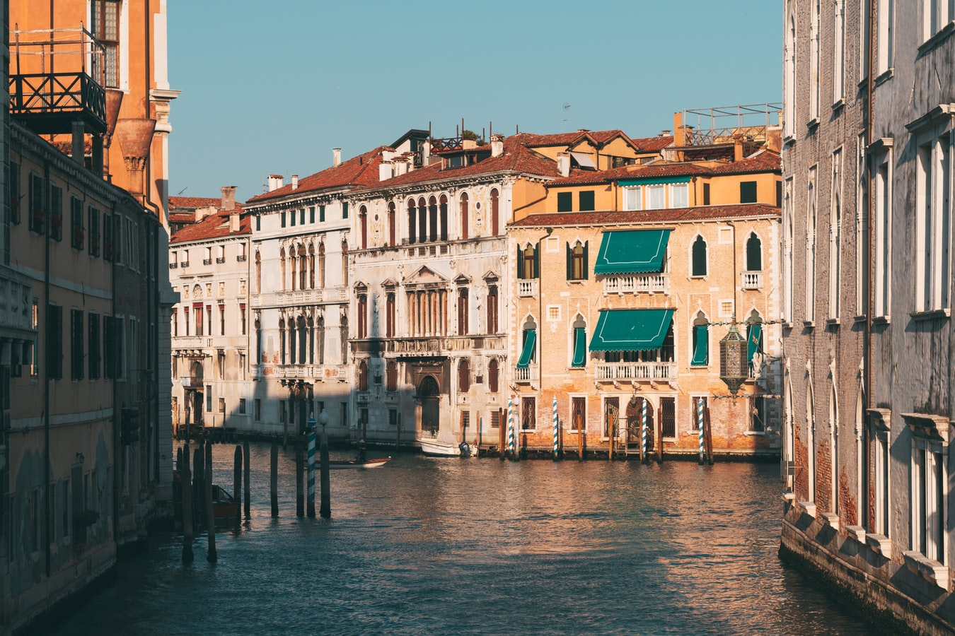 the gorgeous canals in venice with a blue sky and colorful houses