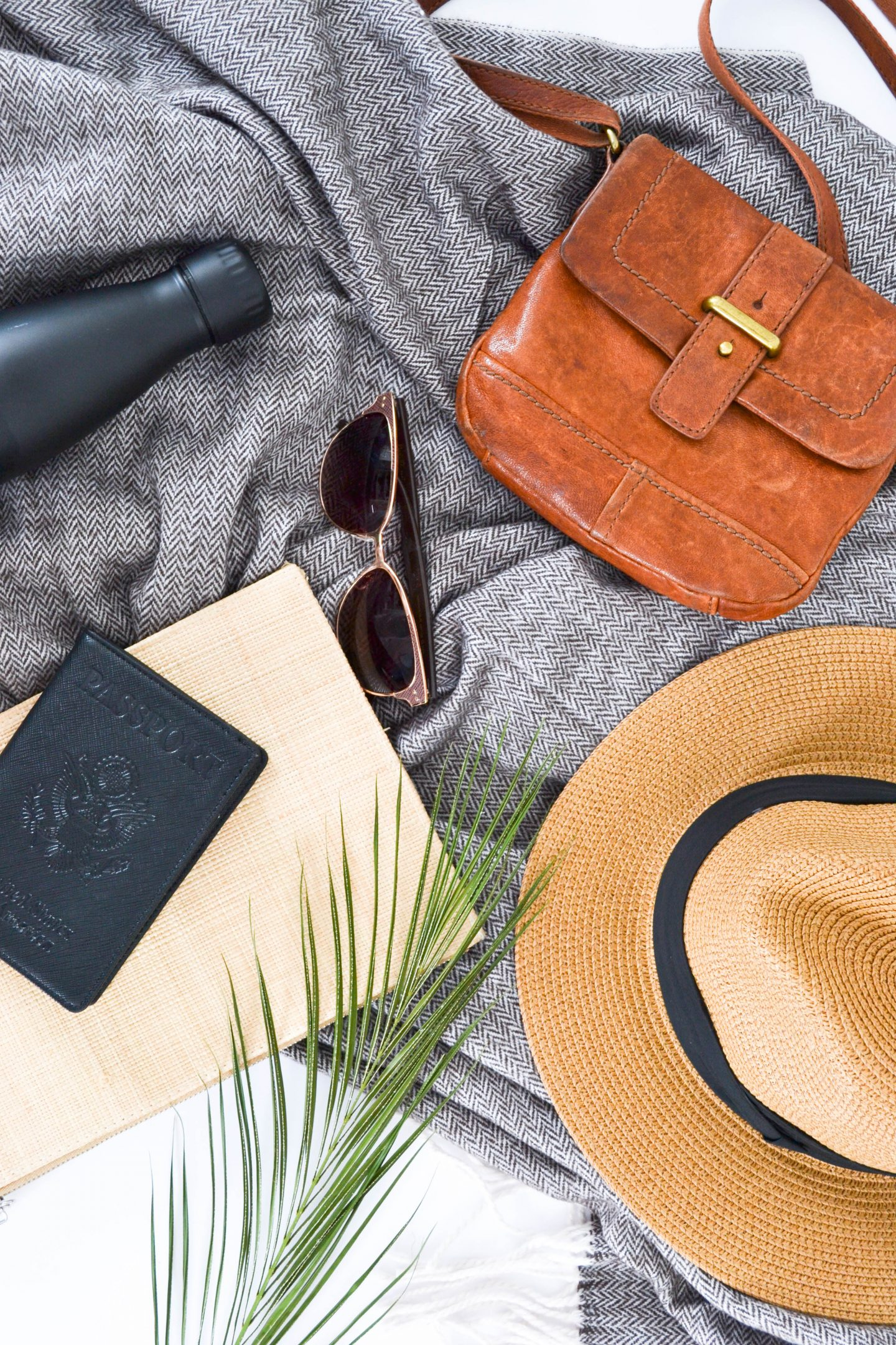 a flatlay with a bag, a hat, a waterbottle, sunglasses and two notebooks