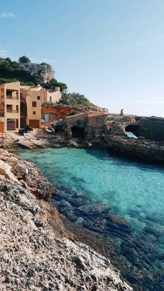 reasons to visit mallorca, ocean with village next to it