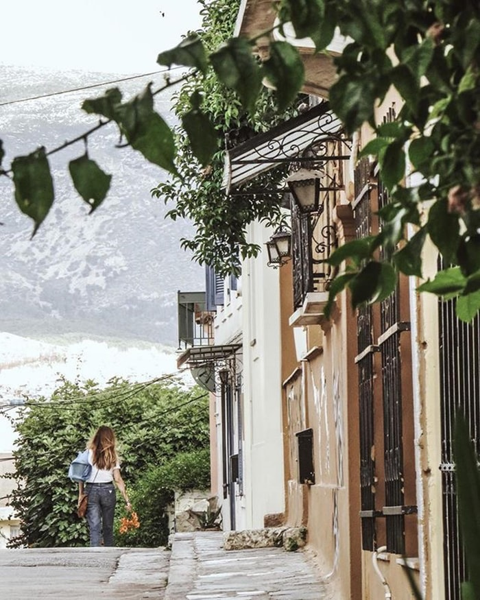 a street with white houses and plants near a lake with a girl giving water to the flowers