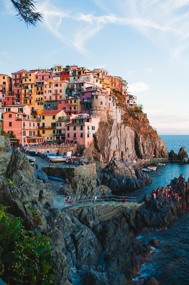 a view over a gorgeous village in cinque terre with colorful houses, the ocean and blue sky