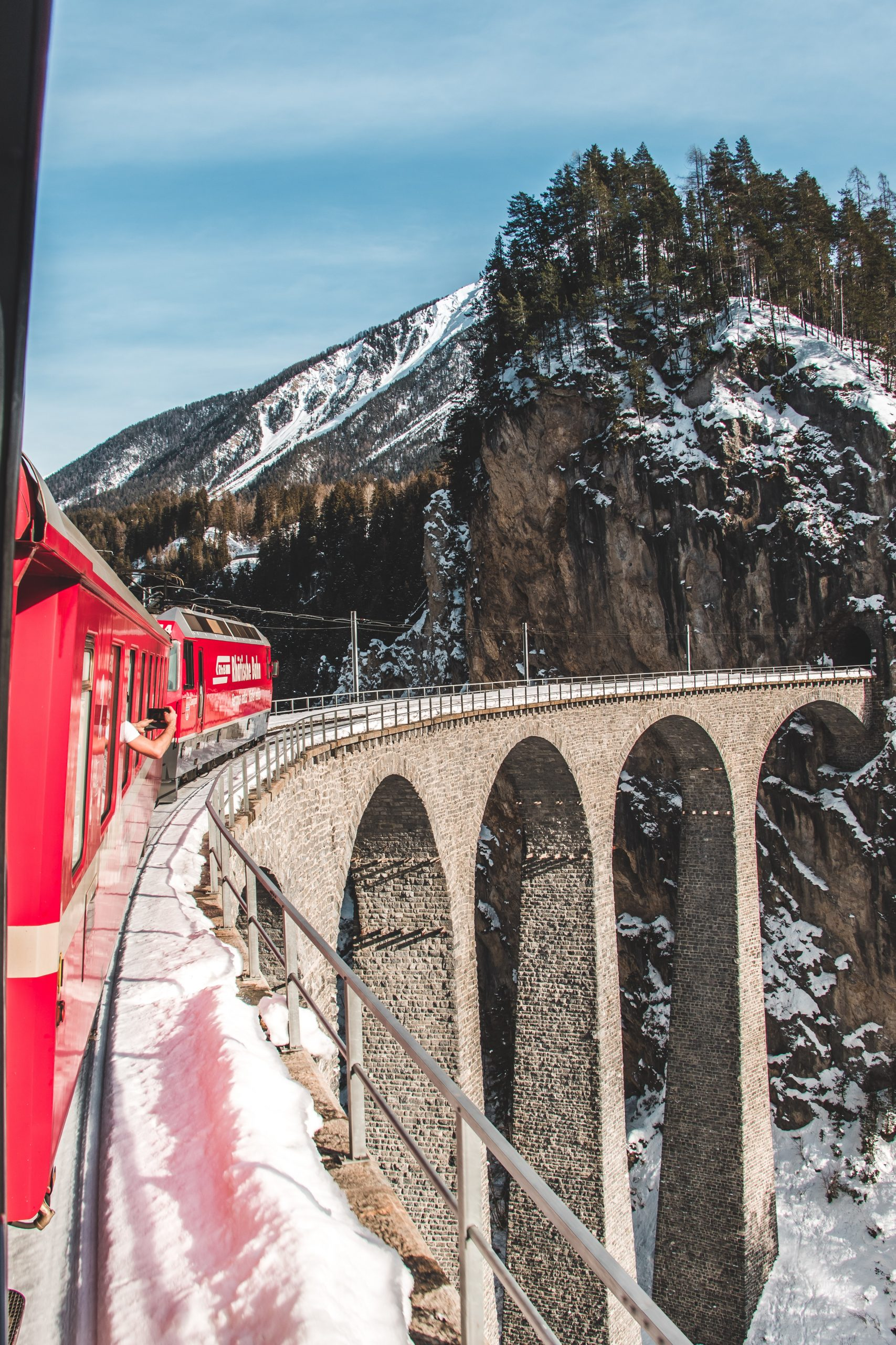 a red train on a bridge in switzerland, scenic train journeys in europe to take next and explore different places in europe