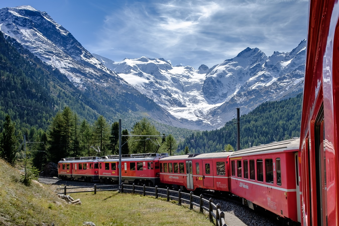 a red train in Switzerland with mountains in the background