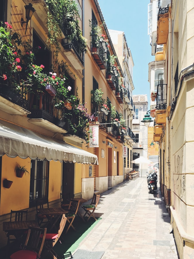 a yellow street in italy or spain with flowers under the windows