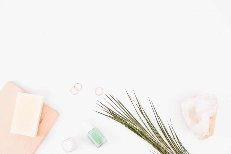 a flat lay of a shampoo bar, nailpolish and essential oil