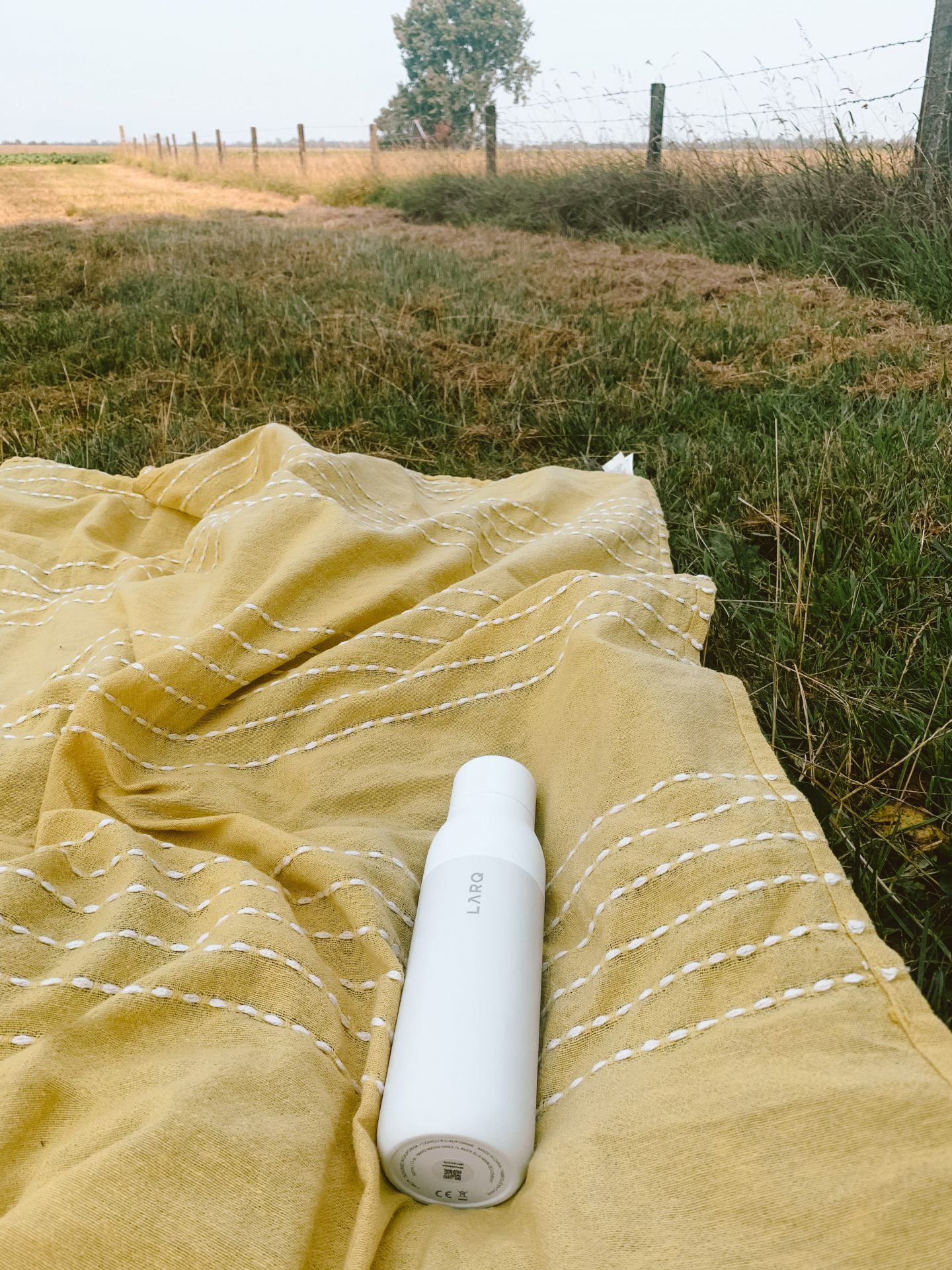 yellow picknick blanket, water bottle from larq, a water filter bottle, purifying water bottle, charger for your bottle, nature