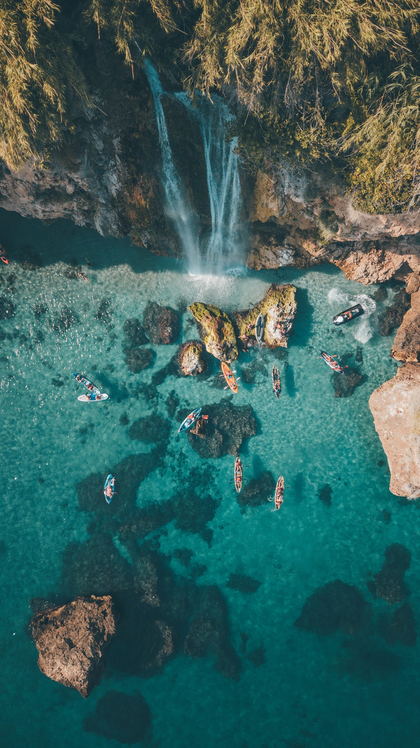 aerial photography over the ocean, waterfall and surfers in the ocean