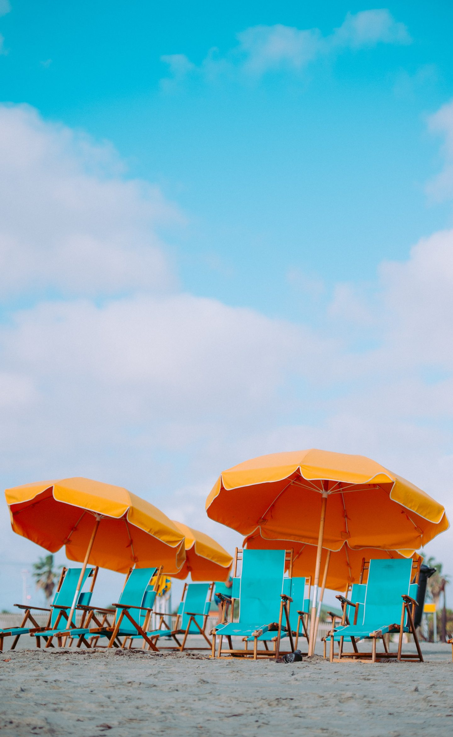 a beach with blue chairs and bright orange umbrellas, blue sky with clouds