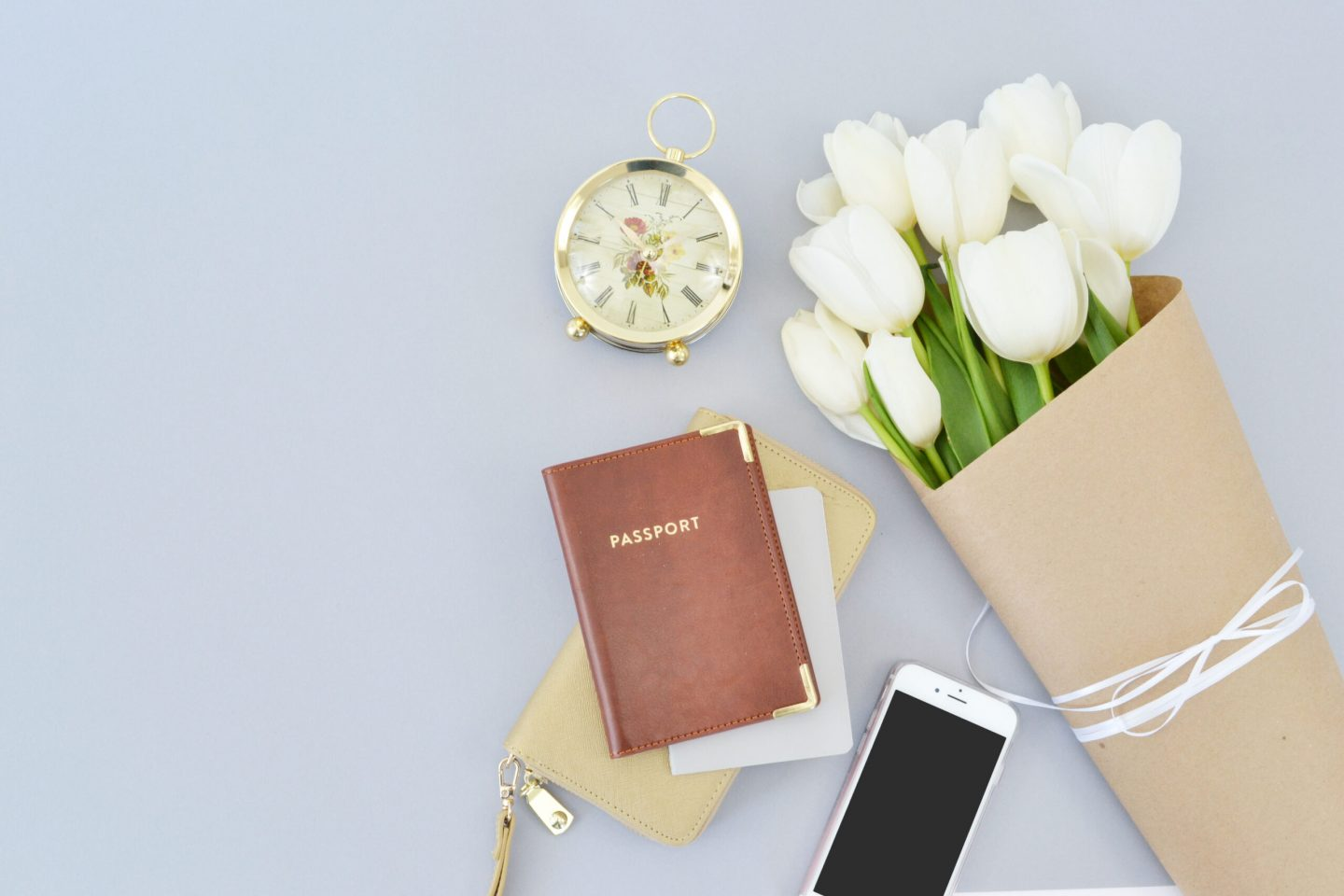 a brown passport wiht flowers, a clock, phone and wallet, travel documents and essentials