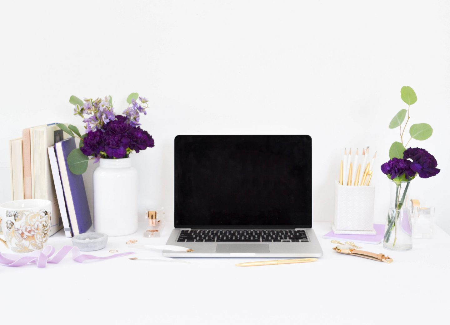 silver colored laptop on a desk with flowers, pencils and a phone