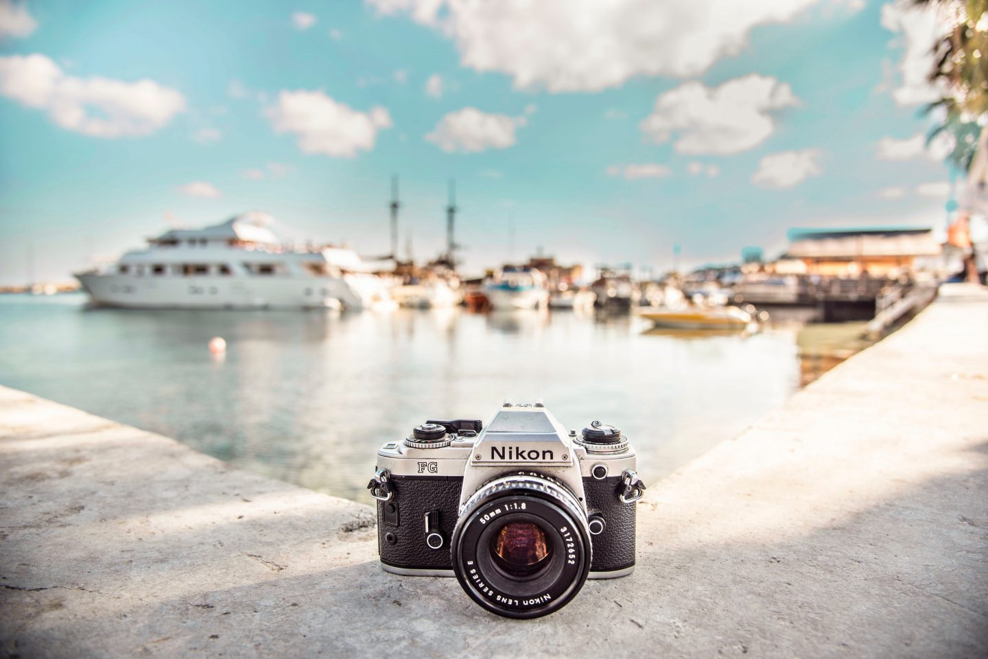 a nikon camera with a harbour and boats in the ocean in the background, blue sky during summer