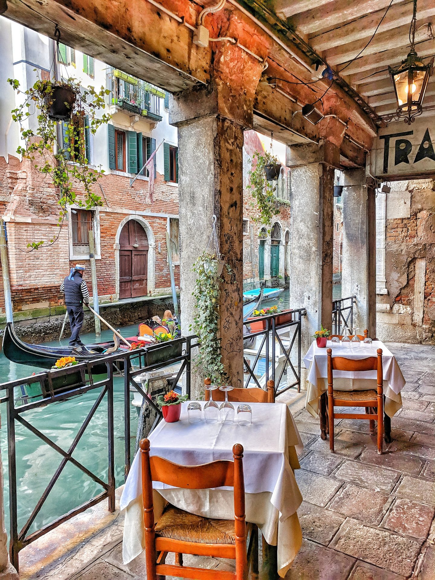 a restaurant in venice next to the canal, travel mistakes to avoid making, colorful photo