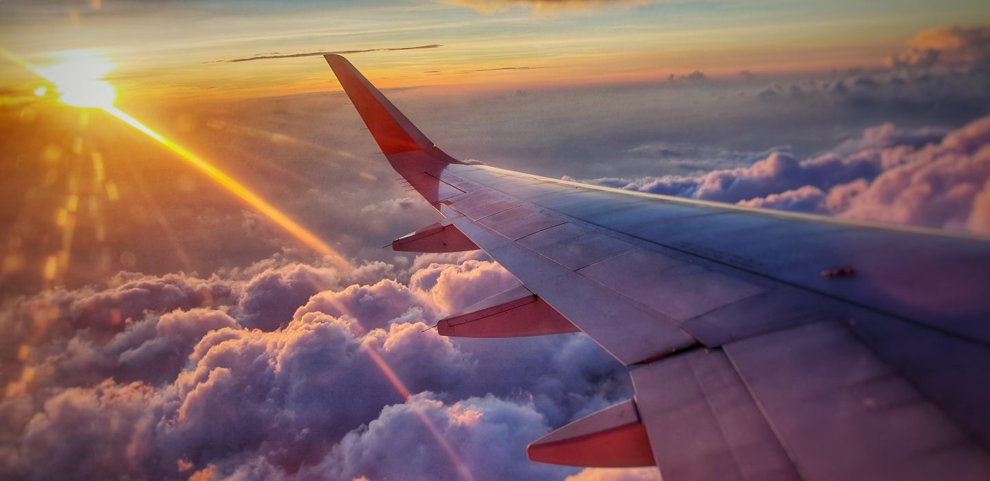 view from airplane window during sunset, clouds, luxury travel
