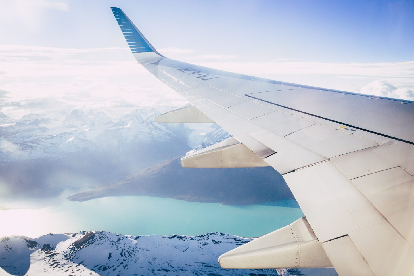 view over the mountains and crystal blue water from the airplane