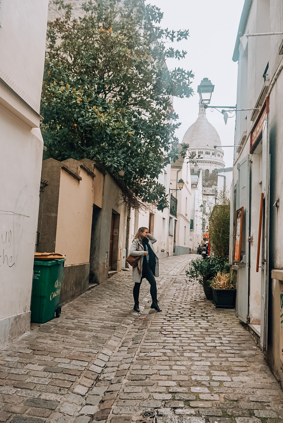 small street in montmartre, view on sacre coeur, girl in paris