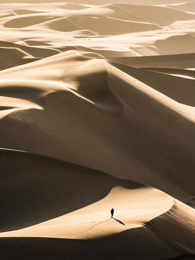 a desert wth hills, man walking with footprints in the sand, desert photography