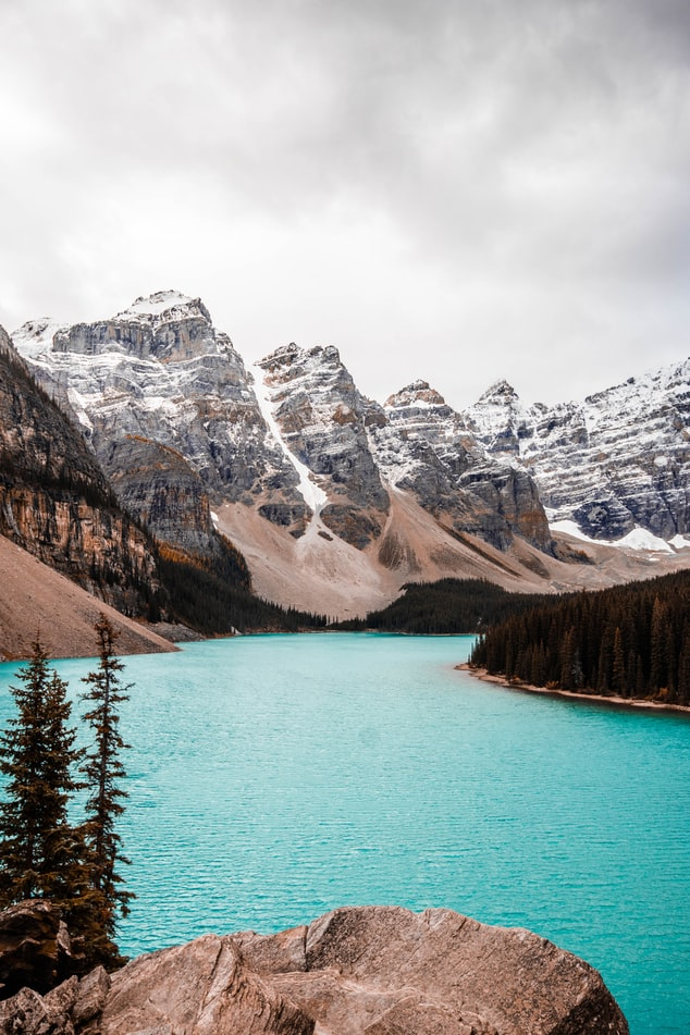 crystal blue lake in canada with snowy mountains the background, travel inspiration