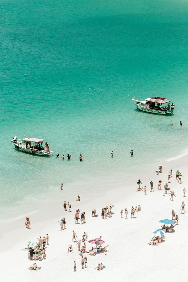 a view over the ocean with boats and people in the water, white sand beach