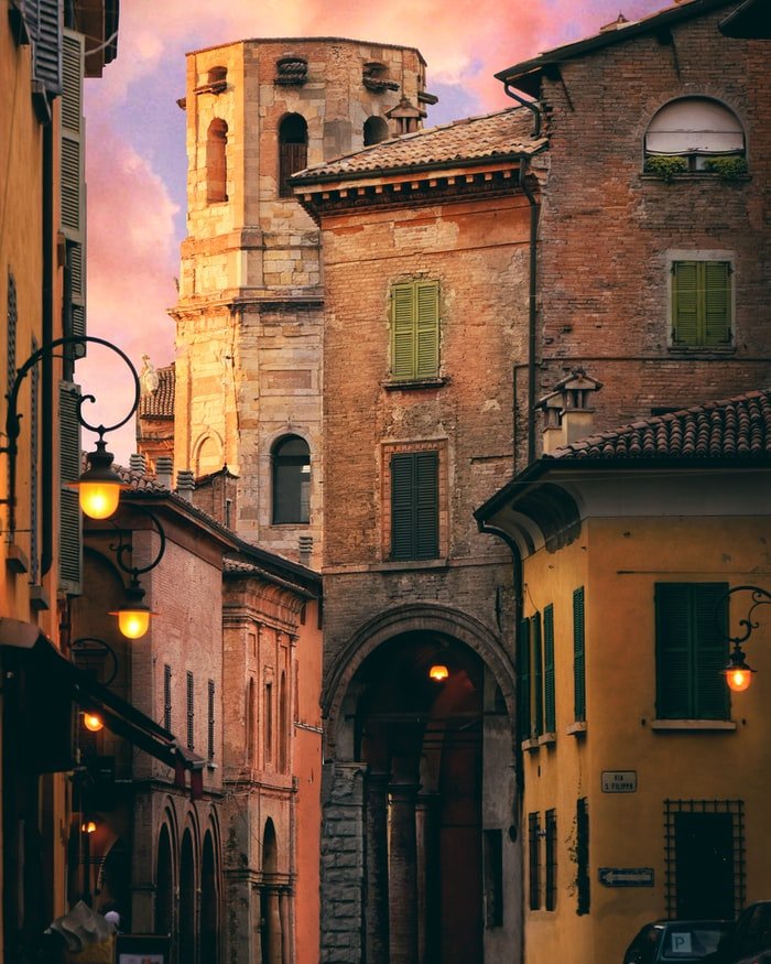 an old street in italy, orange and brown houses, sunset