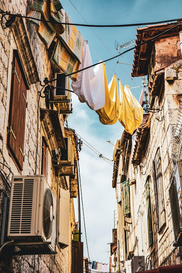 a traditional old street in croatia with laundry on the rooftop