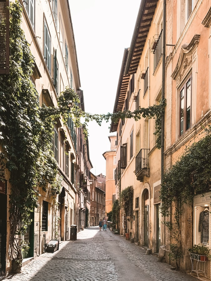 a street in italy, pastel colored houses with greenery