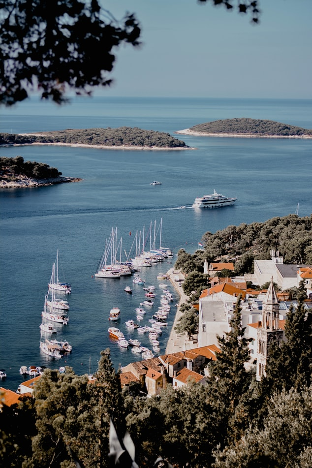 view over the bay, harbour with white boats, islands in ocean, village next to the ocean