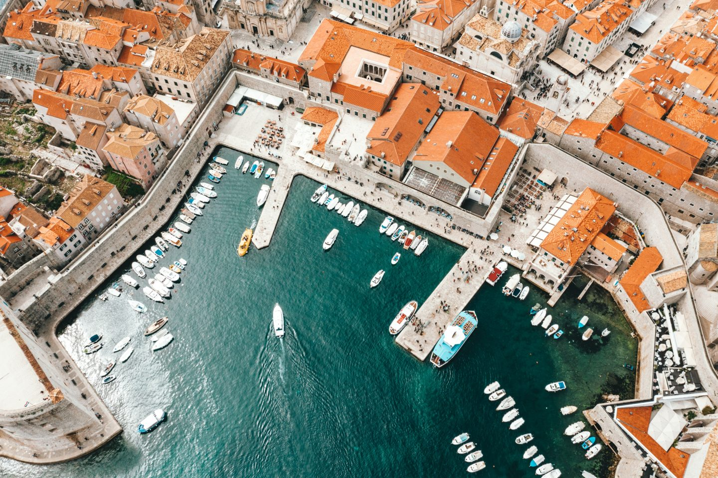 an aerial view over hvar in croatia, a village with white houses and orange rooftop, harbour with white boats