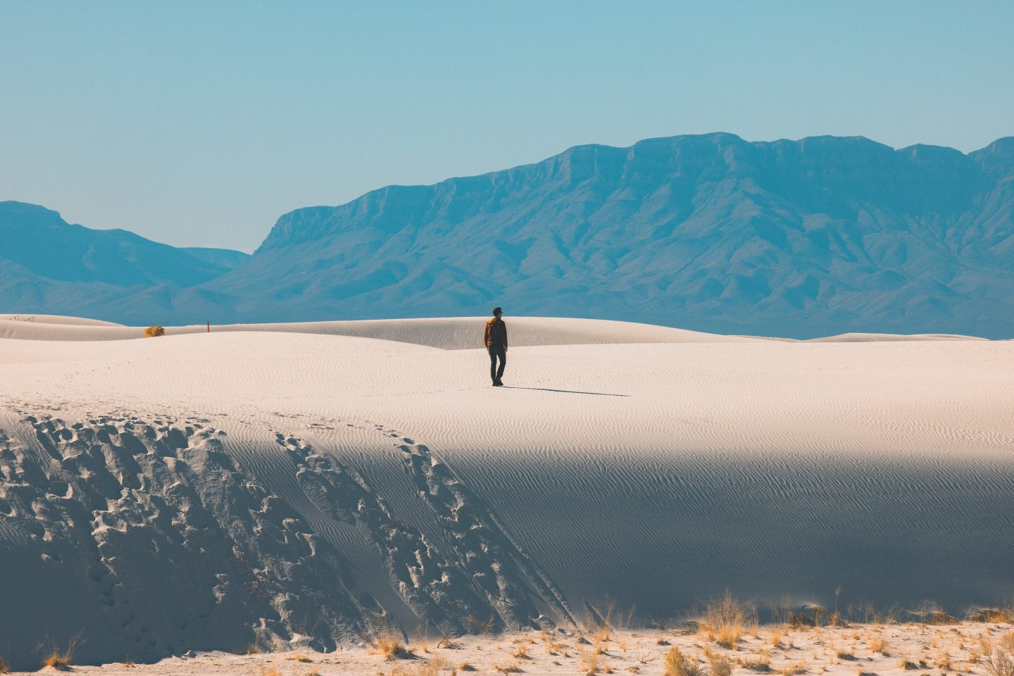 a man walking on sand in the dunes, nature shot