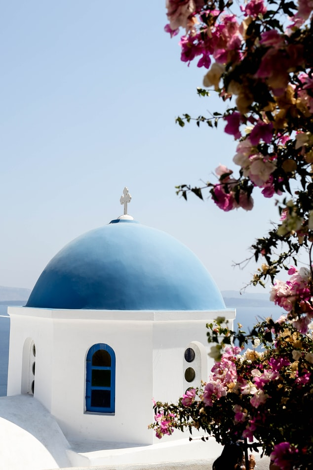 springtime in greece, a view over a church and the ocean, flowers on santorini