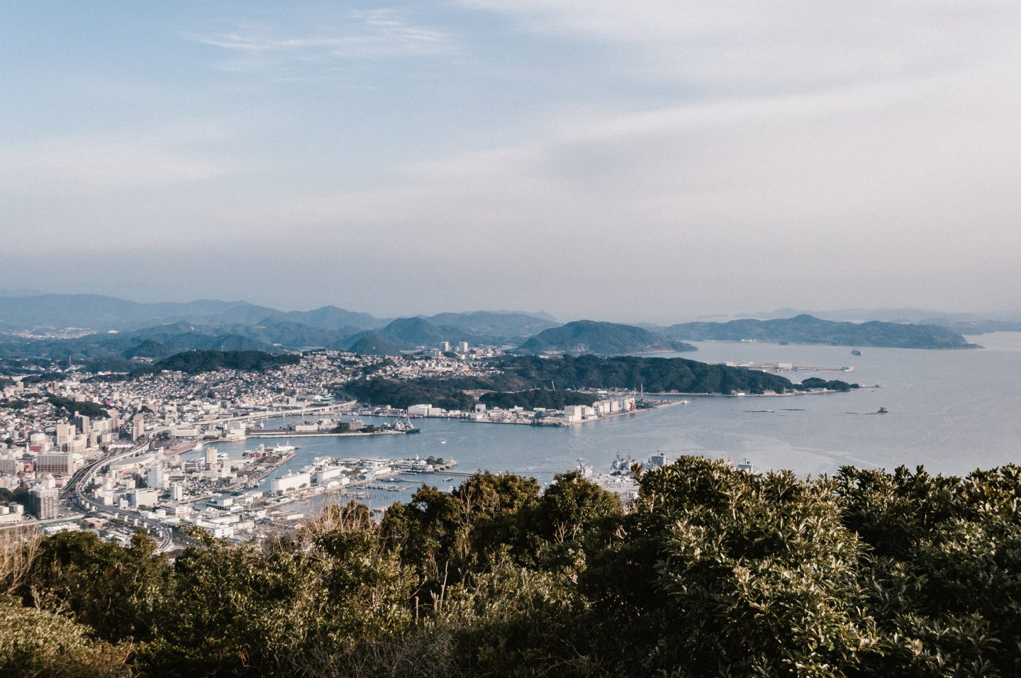 a view from a mountain over the ocean and city, mountains in background, travel scenery